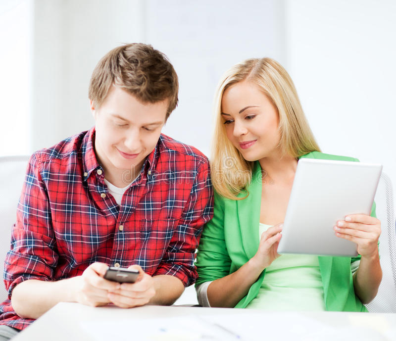 使用智能手机和片剂个人计算机的学生在学校 免版税图库摄影