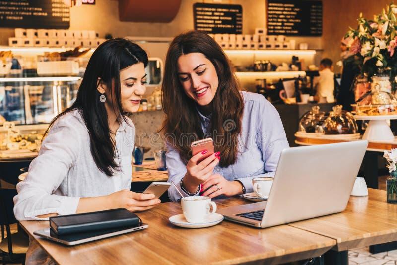 使用智能手机和笑,两名年轻愉快的妇女在咖啡馆坐在膝上型计算机前面的桌上, 免版税库存图片