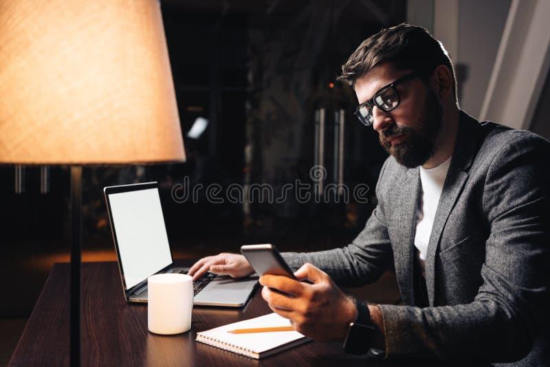 使用智能手机和膝上型计算机的商人在coworking的演播室 工作关于新的起动的年轻有胡子的人在晚上在现代顶楼o 库存照片