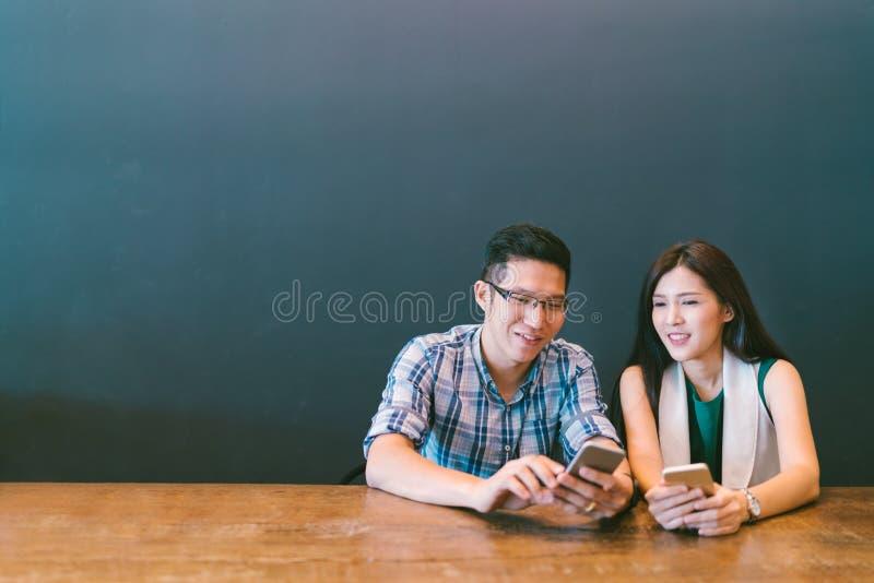 使用智能手机在咖啡馆,与小配件技术的现代生活方式或偶然企业概念的年轻亚裔夫妇或工友 免版税库存图片