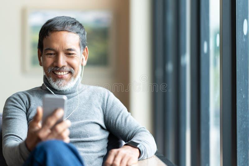 使用智能手机坐的或听的音乐,可爱的成熟亚裔人画象退休了与时髦的短的胡子 免版税库存图片