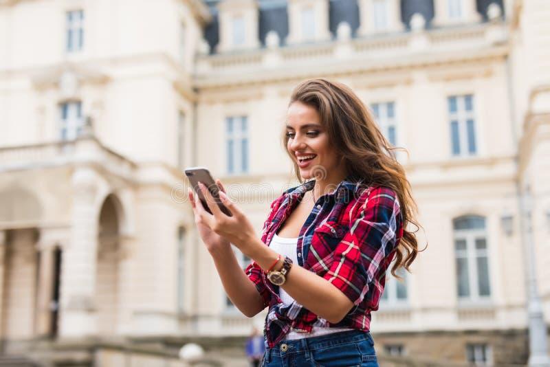 使用智能手机愉快的面孔行家女孩日落时间接触的年轻秀丽妇女旅行 库存图片