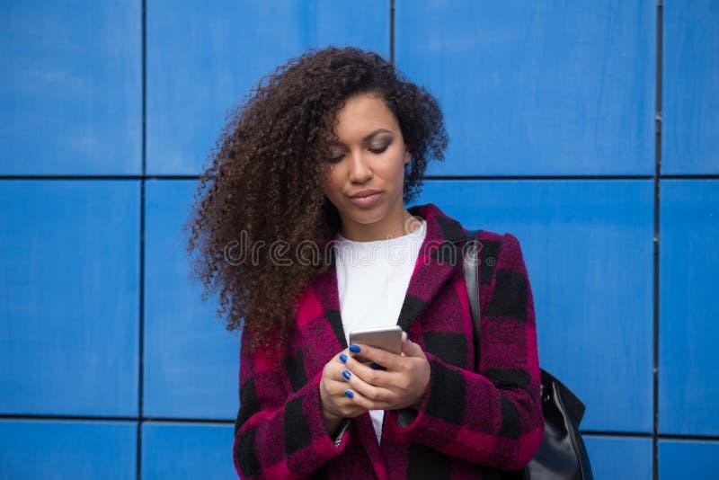 使用智能手机画象的不快乐的少妇 哀伤的女孩读的坏消息或发短信与手机 家庭问题 库存图片