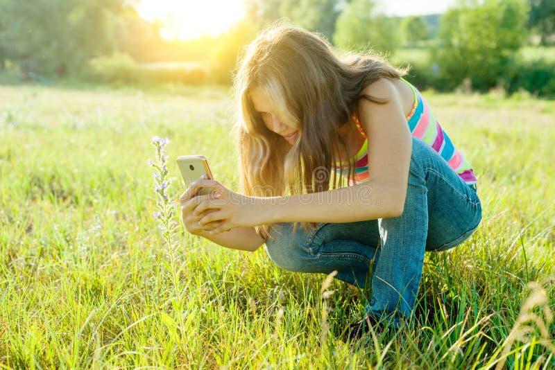 使用智能手机的一个年轻少年女孩的室外画象为她的博克和页在社会网络 免版税图库摄影