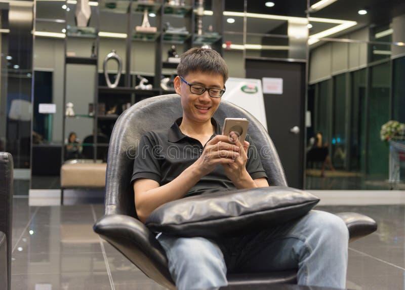 使用智能手机的亚裔人在客厅在晚上 库存图片