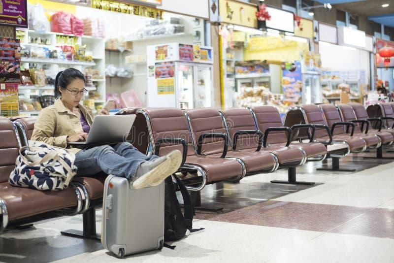 使用智能手机的亚裔妇女少年在机场终端sittin 免版税库存照片