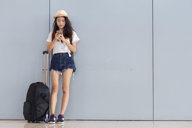 使用智能手机的亚裔妇女少年在机场 库存照片
