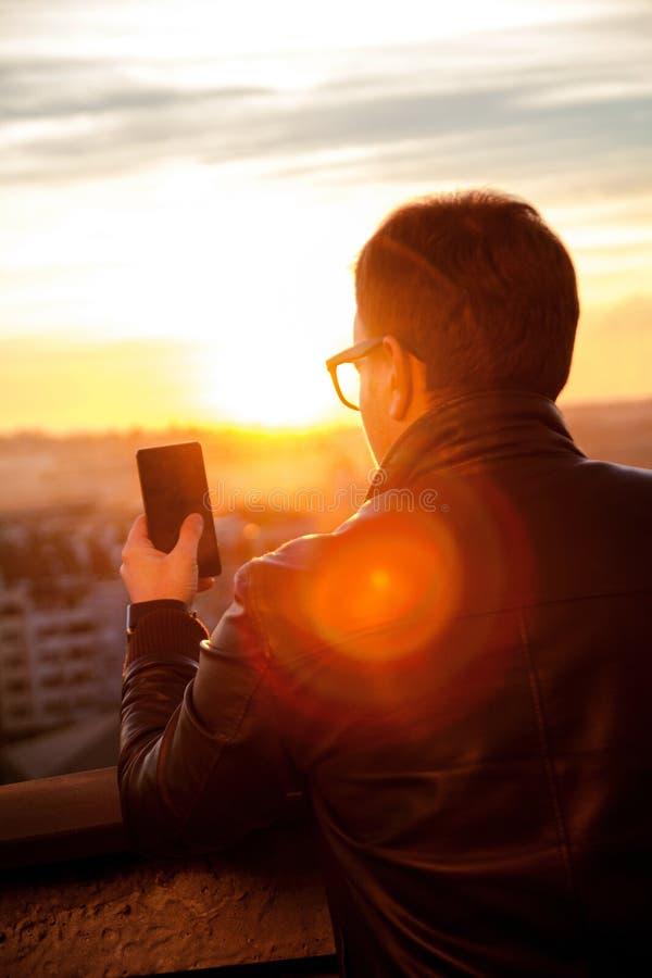 使用智能手机的人和为城市地平线照相 库存照片