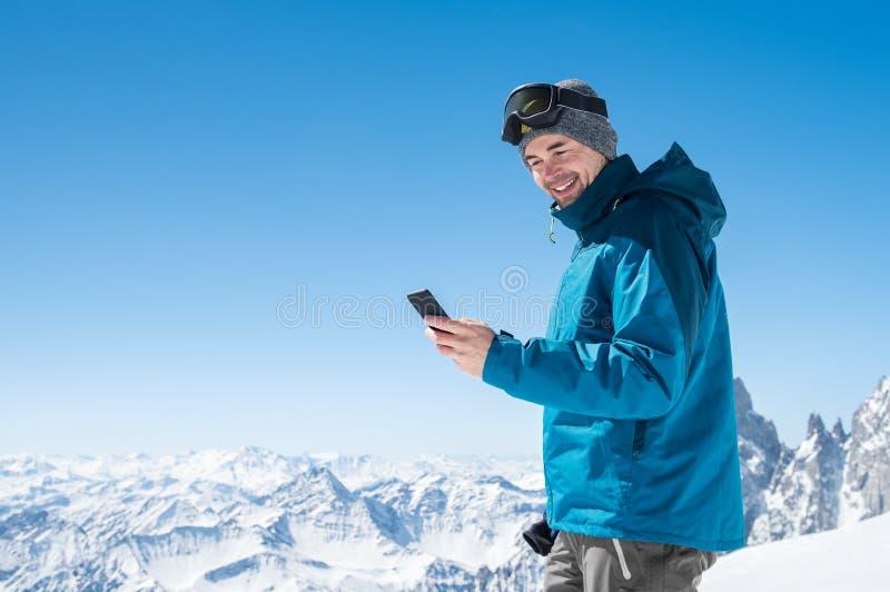 使用智能手机的人在山 免版税库存照片