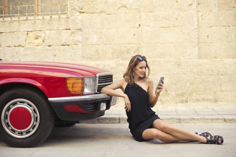 使用智能手机的典雅的女孩在汽车旁边 免版税库存照片