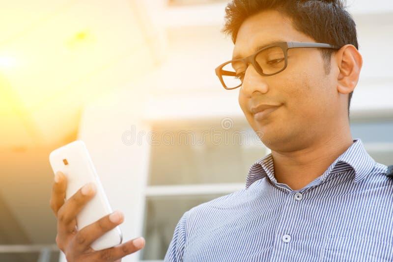 使用智能手机的印地安商人 免版税库存图片