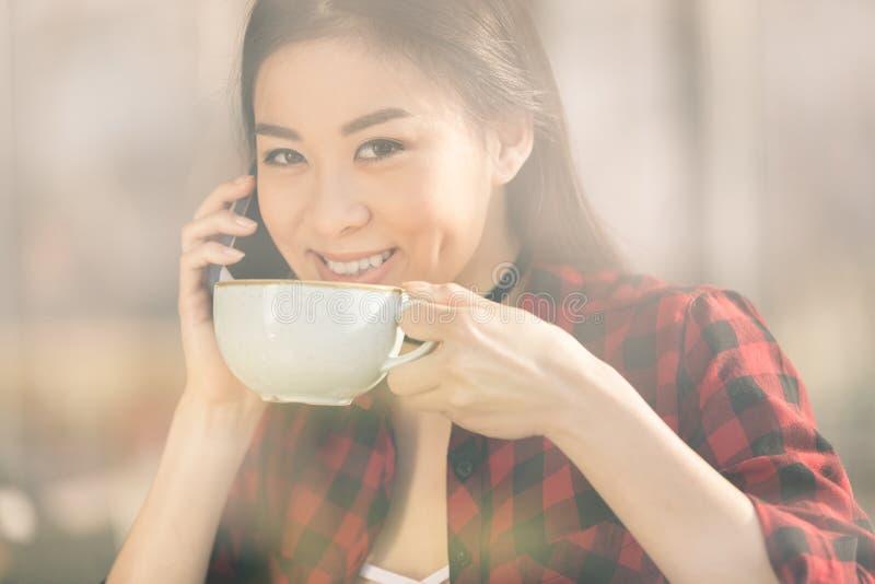 使用智能手机的可爱的亚裔女孩和喝咖啡在咖啡馆咖啡 免版税库存图片