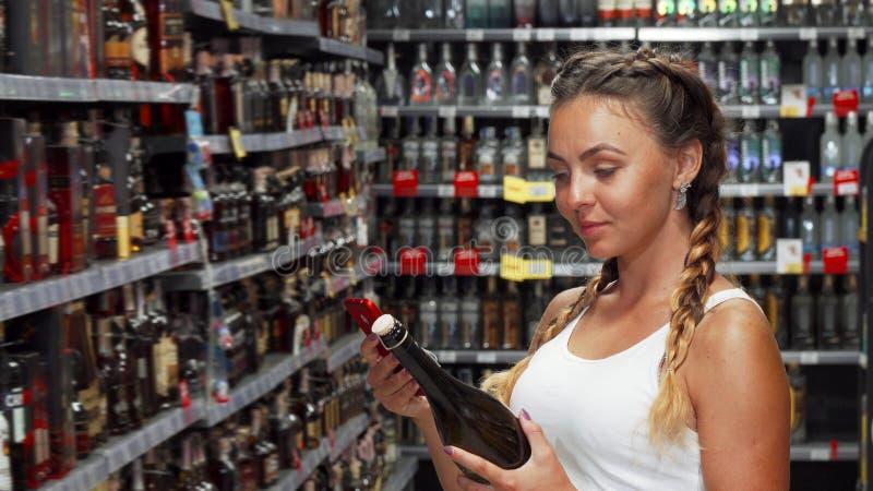 使用智能手机的可爱的妇女在酿酒厂商店 免版税库存照片