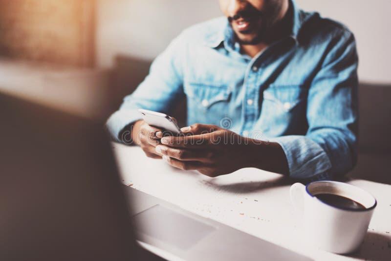 使用智能手机的可爱的有胡子的非洲人,当坐在木桌他的现代家时 人的概念 免版税库存照片