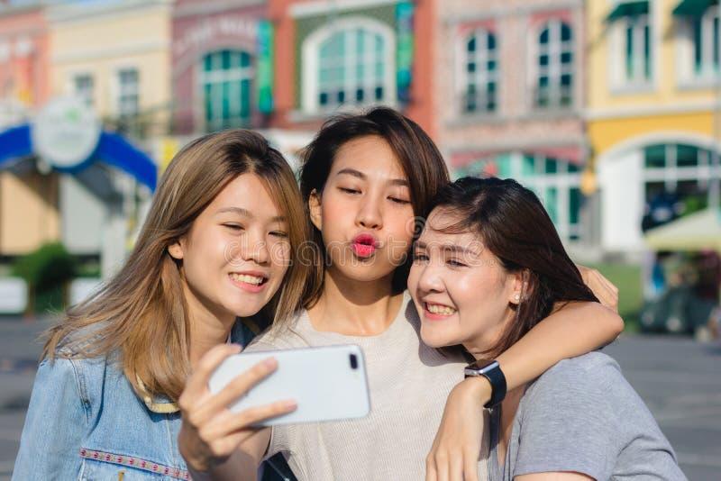 使用智能手机的可爱的美丽的亚裔朋友妇女 愉快年轻亚洲少年在都市城市,当采取自画象时 免版税库存图片