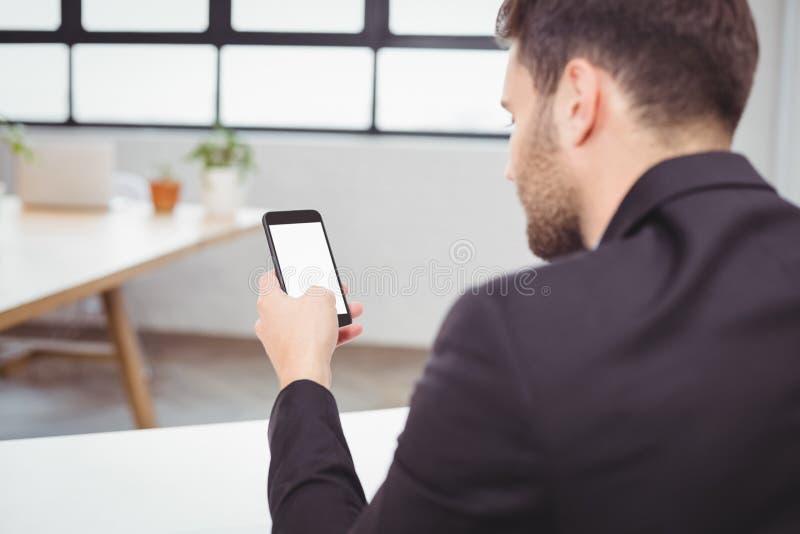 使用智能手机的商人在办公室 免版税库存图片
