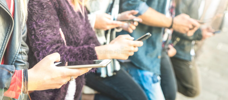 使用智能手机的多文化朋友小组在大学学院后院断裂-流动智能手机使上瘾的人手- 图库摄影