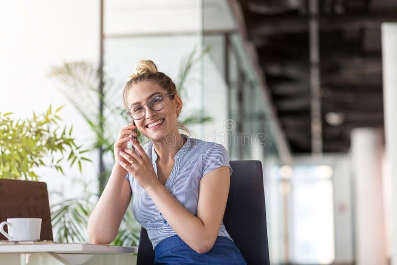 使用智能手机的女商人在办公室 免版税库存照片