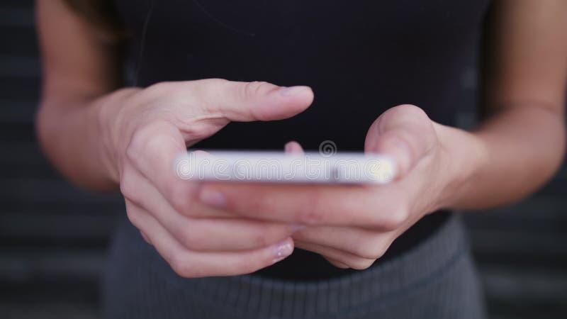 使用智能手机的女商人类型消息,在街道上,特写镜头被射击移动设备在手上,被弄脏的背景 免版税库存照片