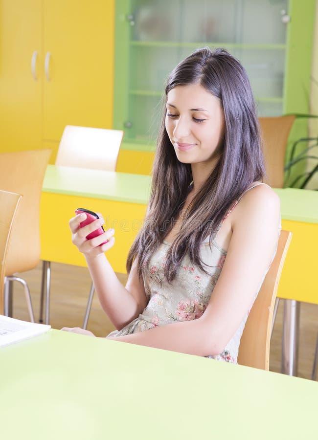 使用智能手机的女学生在教室 免版税库存图片