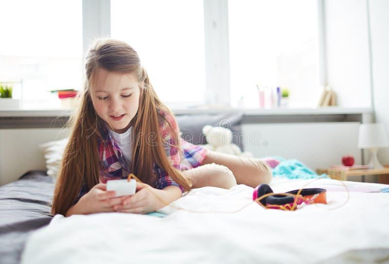 使用智能手机的女孩 图库摄影