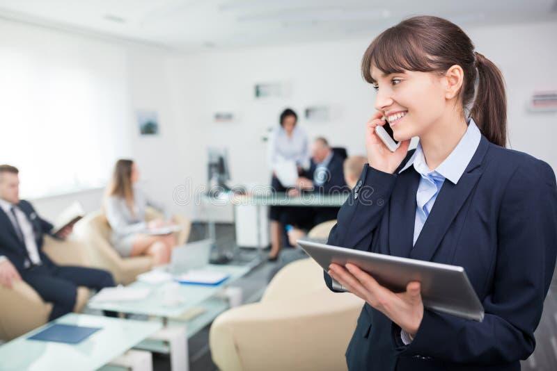 使用智能手机的女实业家,当拿着数字片剂在办公室时 免版税库存照片