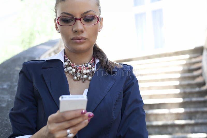 使用智能手机的女实业家 免版税库存照片