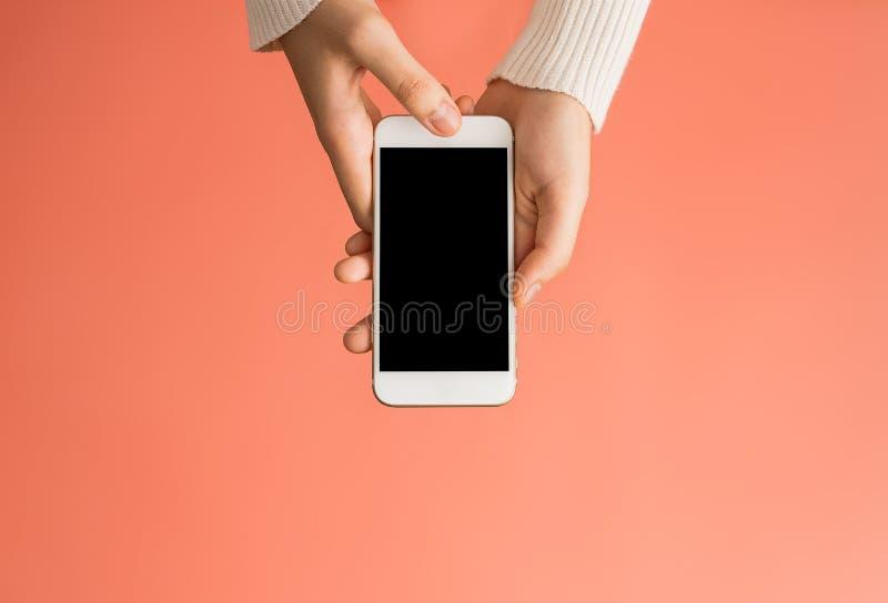 使用智能手机的女性手染黑有橙色backgroun的屏幕 免版税库存照片