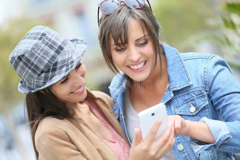使用智能手机的女朋友户外 免版税库存照片