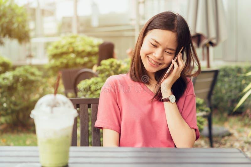 使用智能手机的妇女为在桌上的应用在公园咖啡馆 免版税库存图片