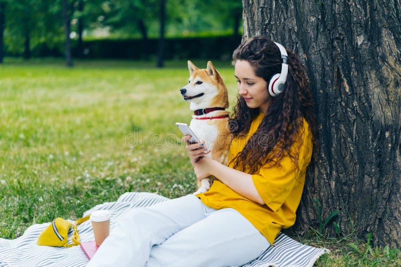 使用智能手机的妇女听到音乐在耳机在有狗的绿色公园 免版税库存照片
