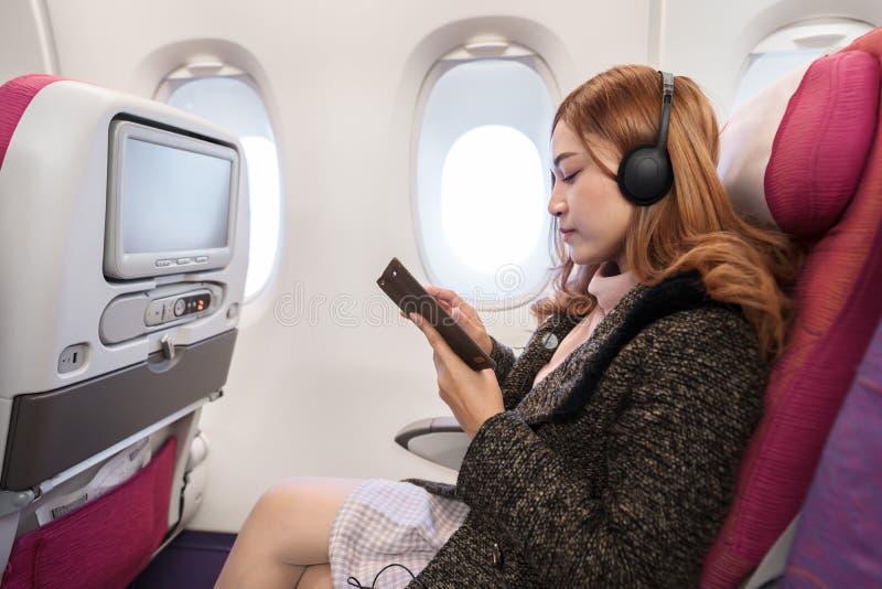 使用智能手机的妇女和听到与耳机的音乐在飞机在飞行中计时 免版税库存图片
