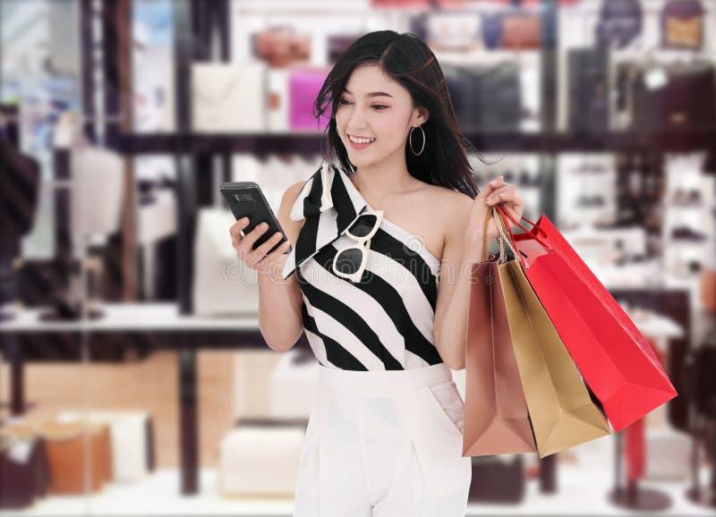 使用智能手机的妇女和拿着购物带来在购物中心 库存图片
