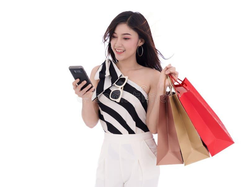 使用智能手机的妇女和拿着购物袋被隔绝在whi 免版税图库摄影