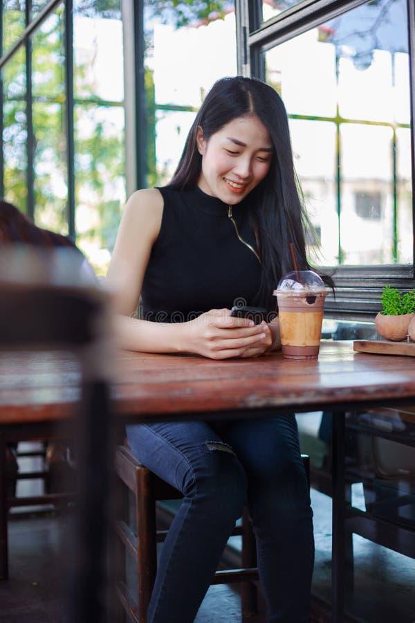 使用智能手机的妇女在咖啡馆 库存图片