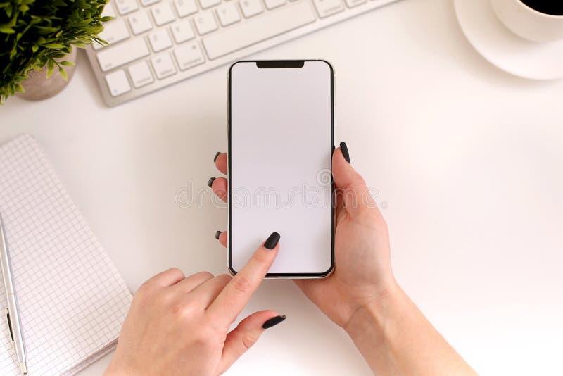 使用智能手机的妇女在工作 白色空的屏幕,顶视图 免版税图库摄影