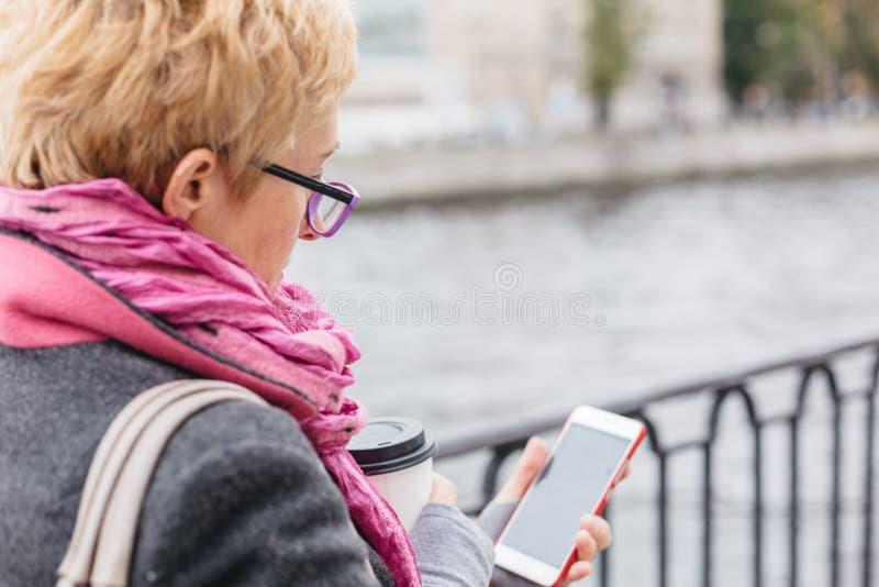 使用智能手机的妇女在河 免版税库存照片