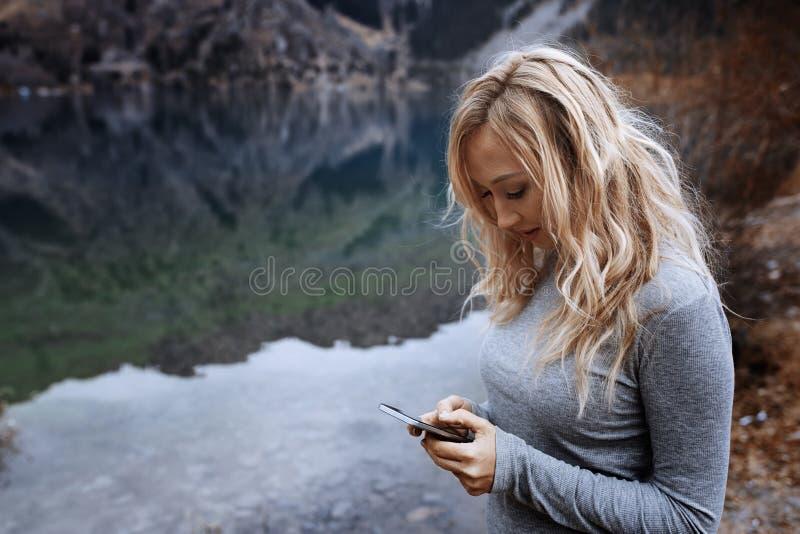 使用智能手机的妇女在湖 免版税库存图片