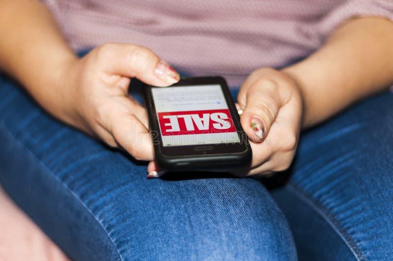 使用智能手机的妇女在网上买某事 企业网上概念 库存图片