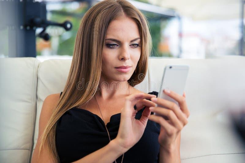 使用智能手机的妇女在餐馆 库存图片
