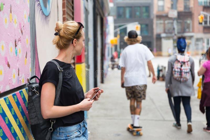 使用智能手机的妇女对五颜六色的街道画墙壁在纽约,美国 免版税图库摄影