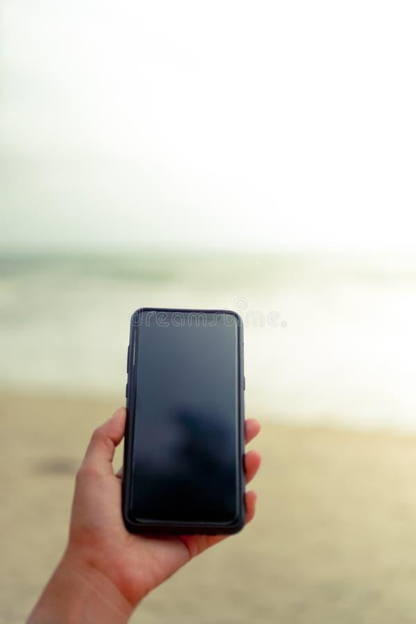 使用智能手机的妇女手在夏天海滩前面 库存照片