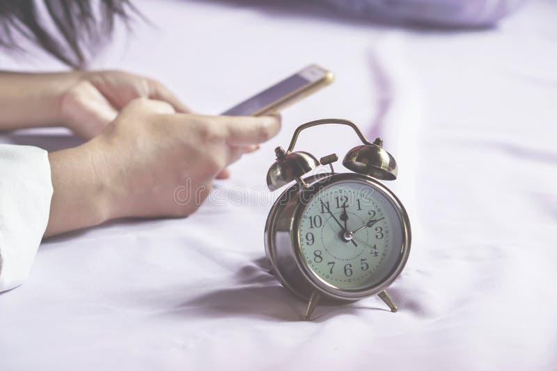 使用智能手机的妇女手在床上 库存图片