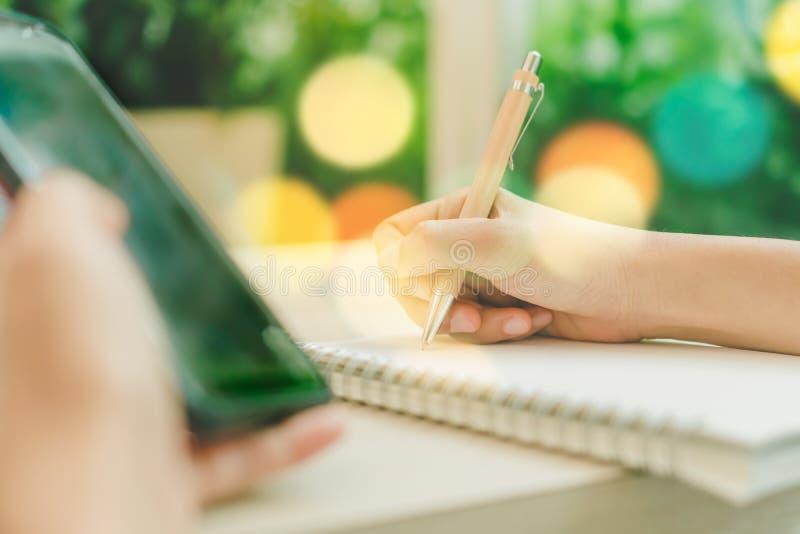 使用智能手机的妇女手对工作研究有咖啡馆商店五颜六色的美好的bokh背景 事务,财政,贸易 免版税库存照片