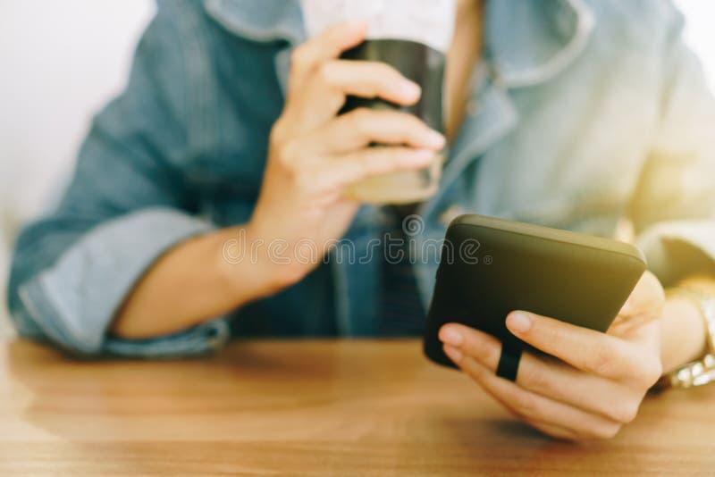 使用智能手机的妇女手,当喝与咖啡馆商店五颜六色的聚焦树荫的咖啡反对美好的backgroun时 库存照片