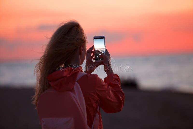使用智能手机的妇女旅客和拍五颜六色的海日落照片  库存照片