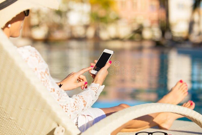 使用智能手机的妇女由水池 免版税库存图片