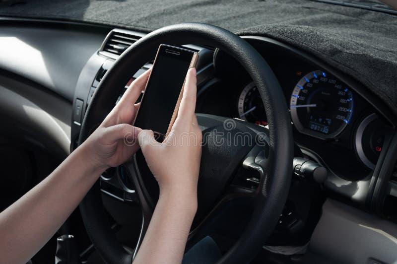 使用智能手机的妇女,当驾驶汽车在驾驶之间,因为上瘾者社交媒介时 库存照片
