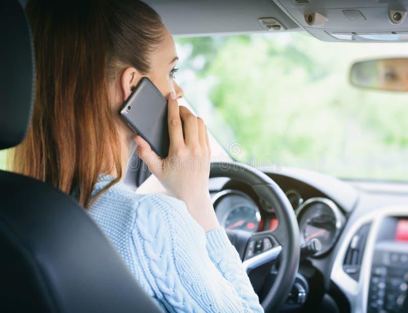 使用智能手机的妇女,当驾驶汽车时 免版税库存图片