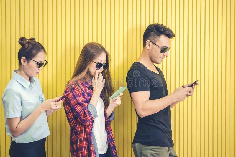 使用智能手机的小组年轻朋友对黄色墙壁,人们由流动智能手机概念使上瘾 库存照片